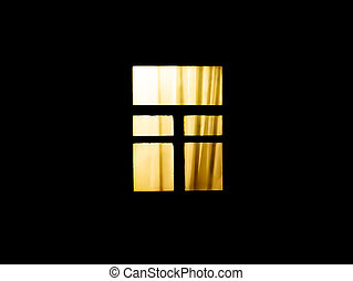 The window of the house glows in the dark at night.