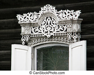 The windows with beautiful architraves in old wooden house. Ulan-Ude.