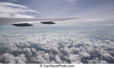 The wing of aircraft moves over the white Cumulus clouds. Sunlight and clear blue sky on the skyline