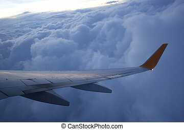 The wing of an airplane above the clouds