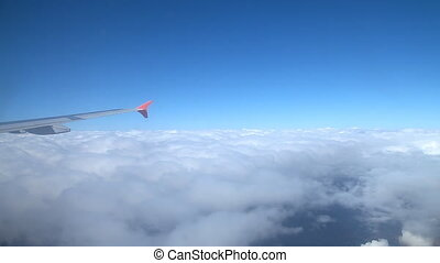 The wing of an airplane flying above the clouds. A view of...