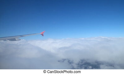 The wing of an airplane flying above the clouds.