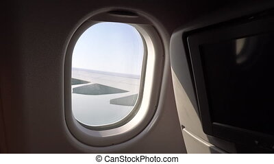 the wing of the aircraft in the window. window with seats on the plane. the cabin of the aircraft. passenger air travel
