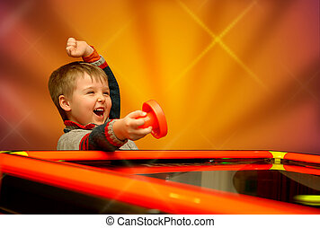 The winner - A child who has won his air hockey game, with a...