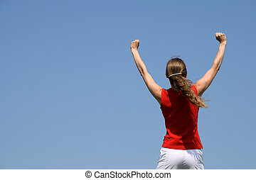 The winner. Energetic young woman with her arms raised in...