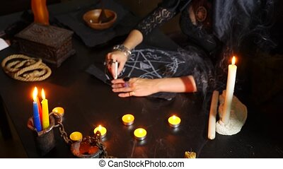 The witch is a fortune teller with candles close-up. A magical ritual. divination. Halloween, 4k, slow-motion