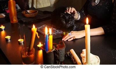 The witch is a fortune teller with candles close-up. A magical ritual with a black cat. Divination. Halloween, 4k, slow-motion.