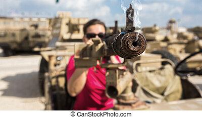 the woman aiming a machine gun