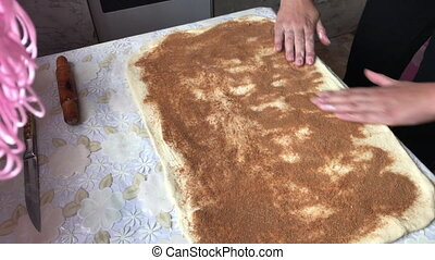 The woman applies a filling of cinnamon and sugar over the surface of the rolled dough. Preparation of buns with cinnamon at home