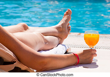 The woman at pool with a juice glass - Glass with orange...