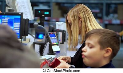 The woman at the cash register, pays for the goods in the supermarket