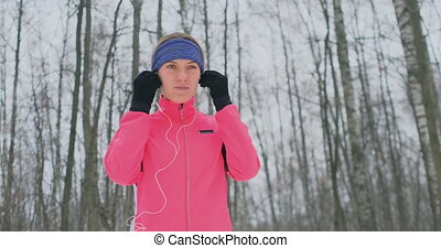 The woman before the morning winter jog inserts headphones...