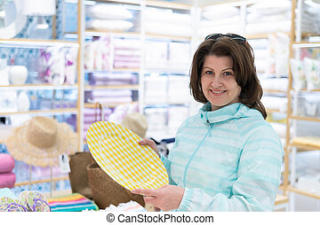 The woman chooses a plate in the store