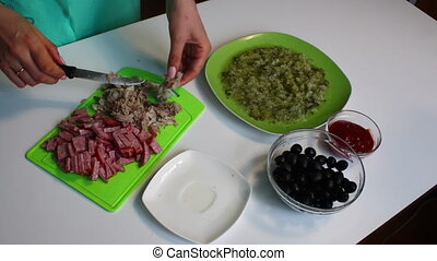 The woman cuts meat into pieces. Soup saltwort. Ingredients for cooking are on the table