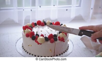 The woman cuts the cake decorated with berries