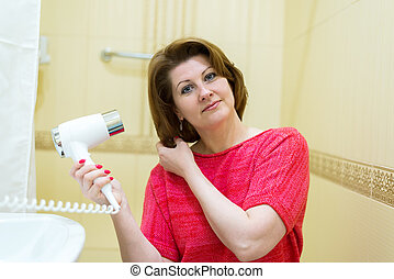 woman dries hair a hair dryer in a bathroom