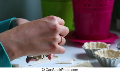 The woman fills the dough with a baking dish. Presses the...