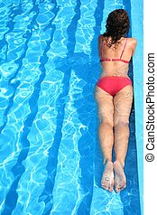 The woman floats in pool