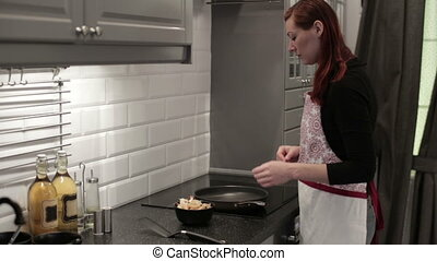The woman fry the shrimp in a skillet