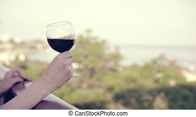 The woman hand hold a glass of red wine, on the winery...
