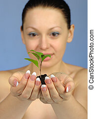The woman holds in hands soil with a plant