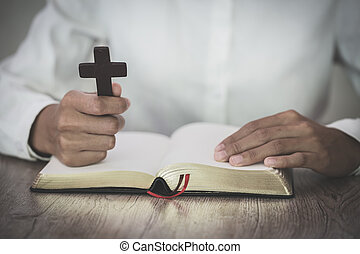 The woman holds the cross and prayes with her scriptures on the table.
