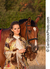 The woman in clothes of 18 centuries with horse