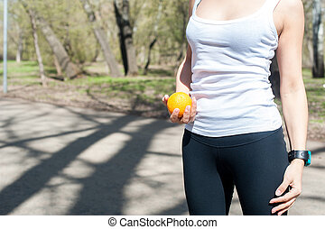 woman in white tank top and black tights holding a orange