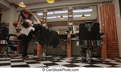 The woman is a professional hairdresser lowers the chair,...