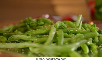 The woman is cooking fresh and tasty green beans in the foil. Sprinkle with lime juice. Close view.