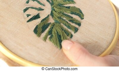 The woman is embroidering a picture of a flower leaf on the ...
