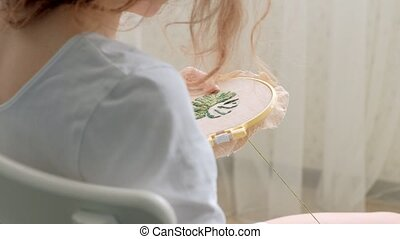 The woman is embroidering a picture of a flower leaf on the...