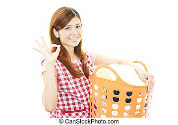 The woman is holding a laundry bask