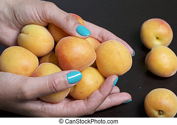 The woman is holding fruit in his hand. A few apricots. On the background of a dark countertop.