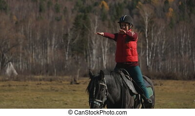 The woman is learning to ride a horse correctly to keep the balance holding her hands parallel to the ground.