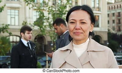 The woman is looking at camera and smiling at background of two men leading business negotiations