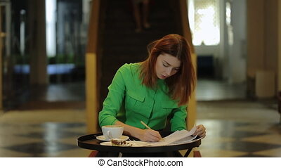 The woman is sitting in cafe working with blueprints leafing over papers correcting numbers