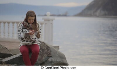 The woman is sitting on the quay located in the coastline of the lake working with tablet pc.