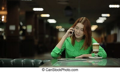 The woman is talking on the cell phone smiling and sitting at the table in the cafe.