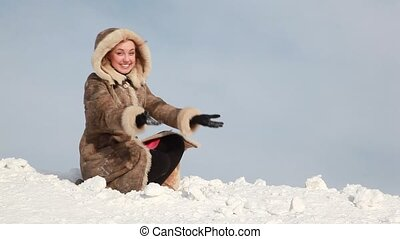 The woman is throwing up snow