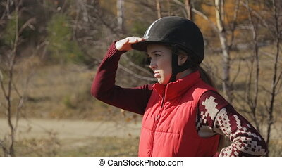 The woman jockey is standing and looking into distance keeping hand as a visor and checking the situation.