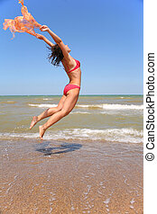 The woman jumps with a scarf.