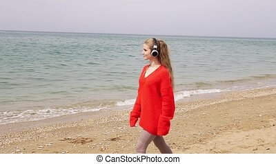 the woman listens to music in large headphones on the beach by the sea