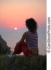 The woman looks at a sunset