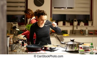 The woman mistress prepares food in the kitchen in the...