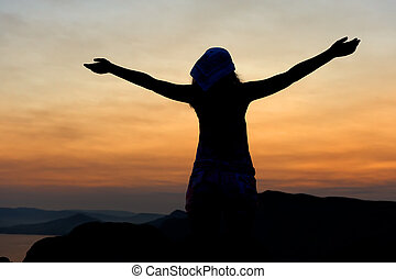 The woman on a mountain with open hands welcomes a decline.