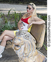 the woman on a stone bench near a stone lion