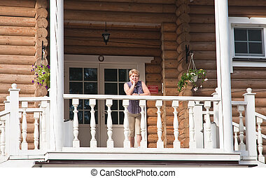 The woman on the balcony of a log cabin