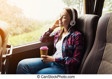 The woman on the passenger seat of the bus listens to music and drinks coffee.