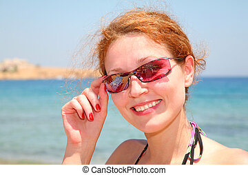The woman on the sea in solar glasses
